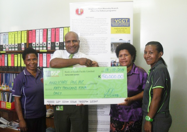 Moses Kewa Manager OH&S Operations, Human Resource BSP (2nd from Left) presenting the dummy Cheque of K50,000.00 to Anglicare National Director Mrs. Heni Meke. Looking on are Rosemary Mawe Corporate Sponsorship Manager - Marketing and Public Relations (R) and Carol Habin PA to the National Director (L). 18th December, 2014
